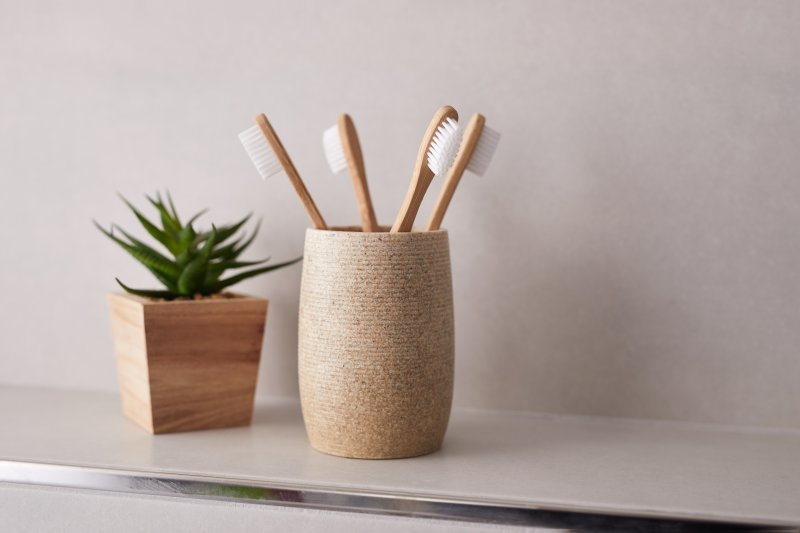 Bamboo toothbrushes sitting in cup on shelf